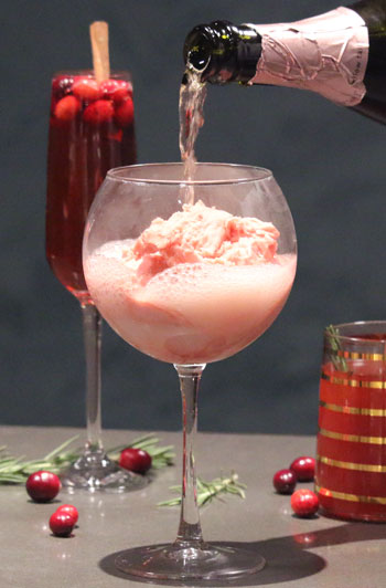 Pink champagne being poured into a large wine glass over a scoop of raspberry sorbet