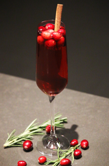 A vanilla cranberry mimosa sits atop a counter with fresh cranberries and rosemary scattered around it