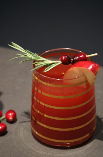 A small glass of cranberry-apple cider punch sits on a counter