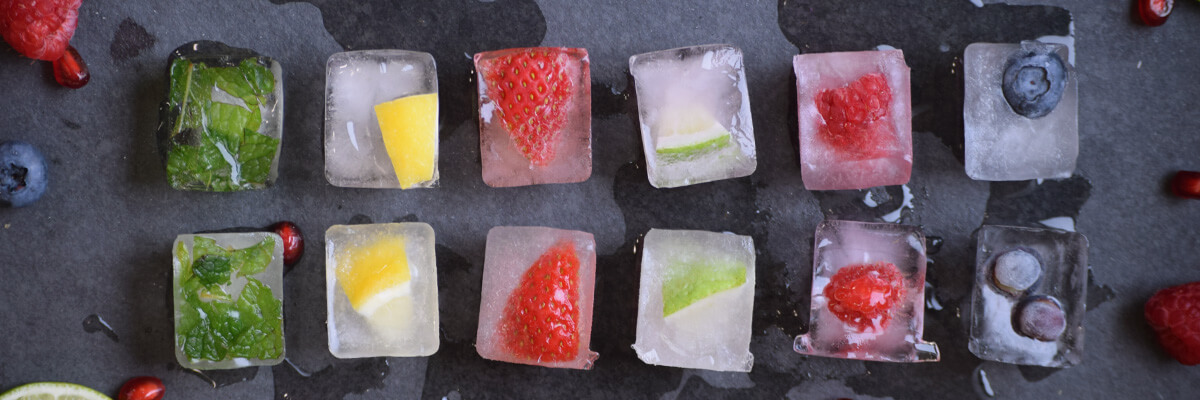 Fresh fruit, vegetables, and herbs frozen in ice cubes that are set up symmetrically on a slate background