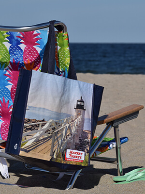 A beach chair sits in the sand at a beach with a Market Basket reusable bag hanging from the back