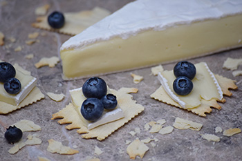 Crackers with brie cheese and blueberries