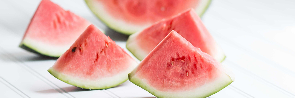 A white table with slices of watermelon standing up on it