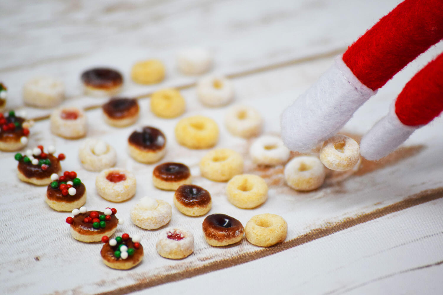 Tiny Elf Donuts with Elf picking up a frosted donut