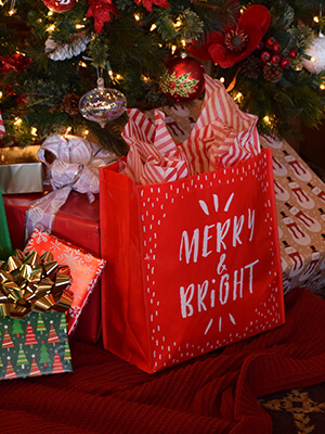 "A ""Merry & Bright"" Market Basket reusable bag sits under a Christmas tree"