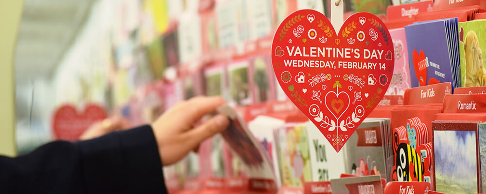 "The greeting card aisle in a Market Basket with a heart shaped red sign that reads, ""Valentine's Day Wednesday, February 14"""