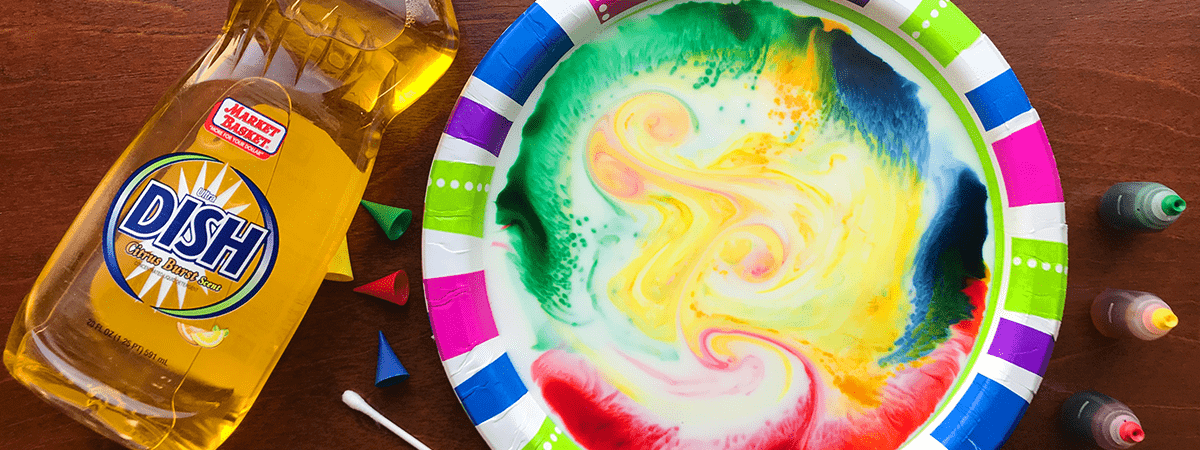 A paper plate filled with a milky kaleidoscope sits on a wooden counter with Market Basket dish soap and food coloring around it