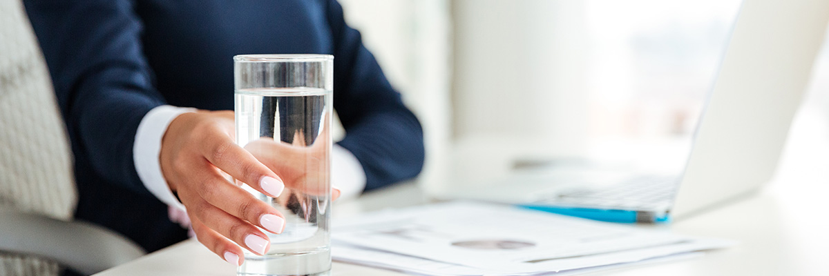 A woman grabs a glass of water that is sitting on her work desk