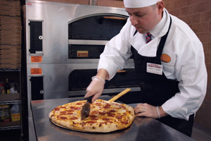 Associate slicing a freshly cooked pizza