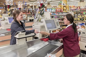 A Market Basket cashier helps a customer