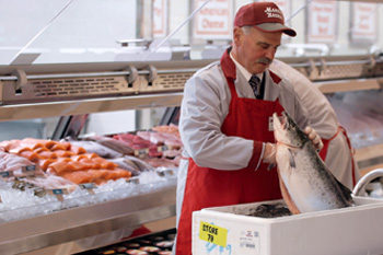 A Market Basket Seafood Manager inspecting the seafood delivery