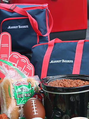 Insulated Market Basket bags sit on a table with chili, Market Basket sub rolls, and a football for a tailgate party